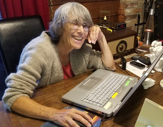 Mary Van Pelt smiling for the camera at her laptop