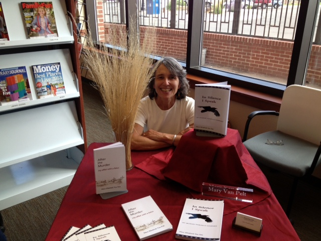 mary sits at book-signing table with display of her books